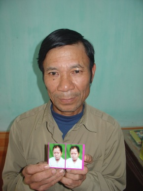 Duan Ton Tat holding a picture of his daughter, Duan Thi Dan