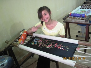 A young girl learns embroidery at Friendship Village