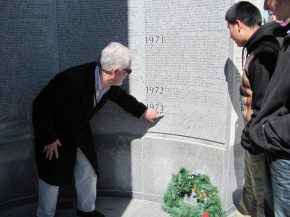 On the left is Franklin Central High School teacher's assistant Keith Diko, Vietnam veteran and field trip chaperone pointing to the last person's name on the list of the Vietnam Veterans' Memorial in Indianapolis.  On the right is FCHS student Miguel Hernandez.