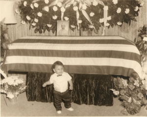 Mario Ybarra, Jr. stands in front of the coffin of his father, PFC Mario Ybarra.