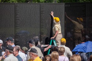 Wall Volunteer Annmarie touches The Wall before she makes a name rubbing during Memorial Day weekend, 2014.