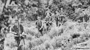 oldiers of the 6th Battalion, The Royal Australian Regiment (6RAR), push through dense scrub country in search of retreating Viet Cong. This photograph was taken the day after the battle. CUN/66/0693/VN