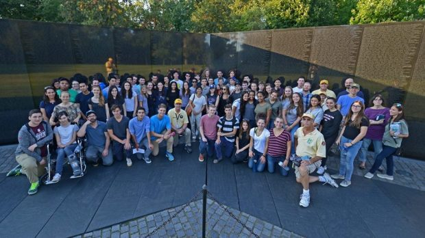 Maya Lin poses with students in front of The Wall, made in her design.
